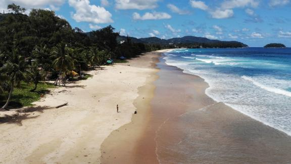 An aerial photograph shows a lone visitor on Karon Beach on June 30, 2021 one day before the Phuket Sandbox tourism scheme that allows visits by people vaccinated against the Covid-19 coronavirus is set to launch. (Photo by Lillian SUWANRUMPHA / AFP) (Photo by LILLIAN SUWANRUMPHA/AFP via Getty Images)