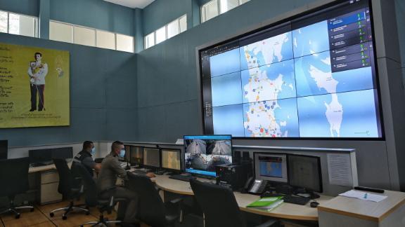 Policemen look at maps of Phuket on monitors set up to track tourist movements at the Phuket Sandbox Control Center on June 30, 2021.