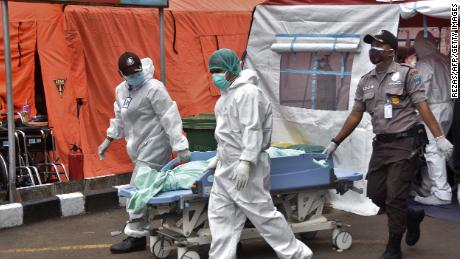 Medical staff carry a body of a patient who died of Covid-19 at a hospital in Bekasi on July 1, 2021.