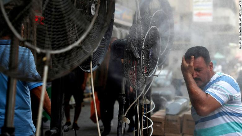 A man stands by fans spraying mist along a street in Iraq's capital, Baghdad, on June 30.