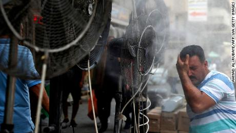 A man stands by fans spraying fog on a street in the Iraqi capital, Baghdad, on June 30.