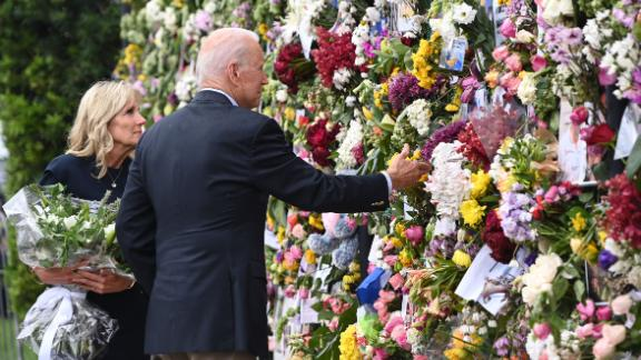 """President Joe Biden and first lady Jill Biden visit a memorial near the partially collapsed building on July 1. <a href=""""https://www.cnn.com/2021/07/01/politics/joe-biden-south-florida-visit/index.html"""" target=""""_blank"""">Biden traveled to Surfside</a> to console families still waiting on news of their loved ones. Those meetings were closed to the press."""