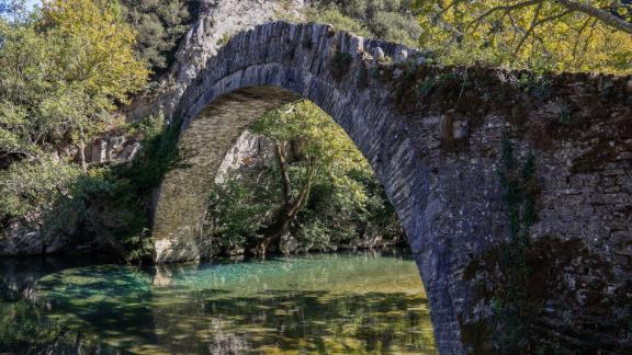 Uma velha ponte de pedra atravessa o rio Voidomatis.