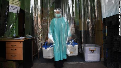 A health worker delivers containers of Sinovac vaccines from a cold room in Bandung, Indonesia.