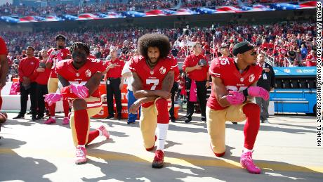 Colin Kaepernick, center, and two other members of the San Francisco 49ers kneel during the national anthem prior to a game against the Tampa Bay Buccaneers on October 23, 2016, in Santa Clara, California.