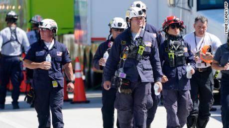 Члены городской и спасательной команды Южной Флориды идут недалеко от южных башен Шамплейн.