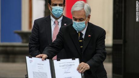 Chilean President Sebastian Pinera shows the official document that calls on the National Assembly members that will draft a new constitution to meet for their first session on July 4, at La Moneda presidential palace in Santiago, Chile, Sunday, June 20, 2021.