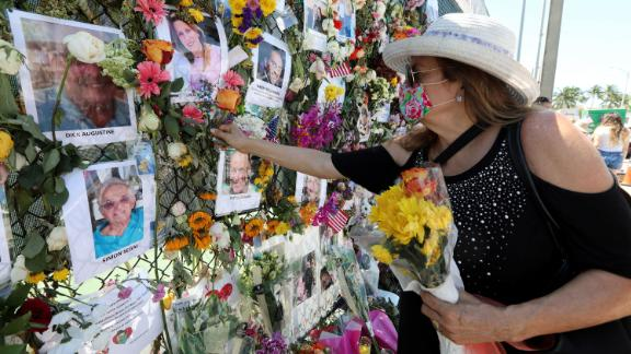Karol Casper places a flower on the memorial wall set up near the building.