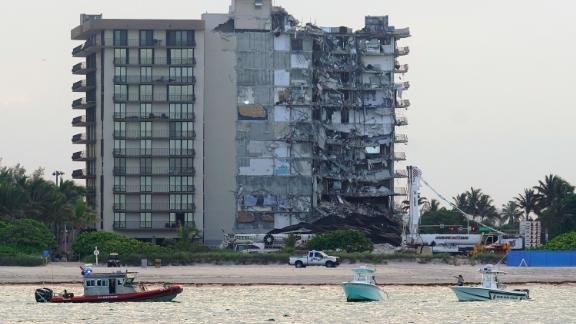 A U.S. Coast Guard, left, and a Miami-Dade County Police boat, right, patrol the ocean in front of the partially collapsed Champlain Towers South condo building, where demolition experts were preparing to bring down the precarious still-standing portion, Sunday, July 4, 2021, in Surfside, Fla. The demolition work has suspended the search-and-rescue mission in the rubble below, but officials said it should eventually open up new areas for rescue teams to explore.