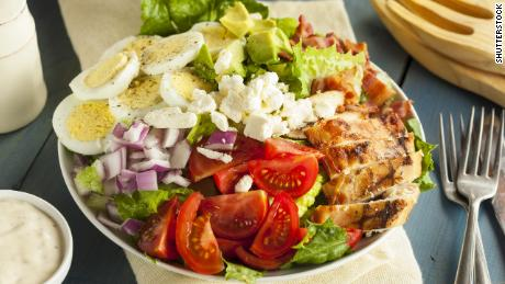 This hearty Cobb salad features chicken, bacon, t tomato, onions and eggs.