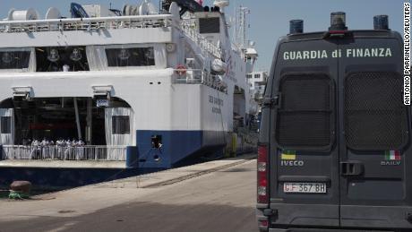 """Een Italiaans politievoertuig geparkeerd naast het schip """"  Geo Barentsz """"  Terwijl de migranten op 18 juni op Sicilië wachten om van boord te gaan."""