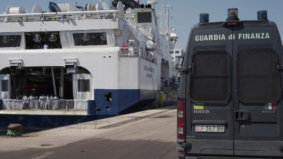 An Italian law enforcement vehicle parked next to the ship