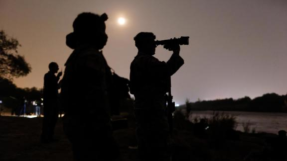 Texas National Guard troops scan the Mexican side of the Rio Grande for immigrants preparing to cross on April 27, 2021 in Roma, Texas.