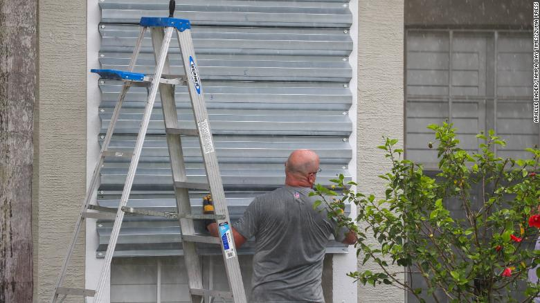 A Tampa resident covers his windows with hurricane shutters in preparation for Hurricane Elsa Tuesday.