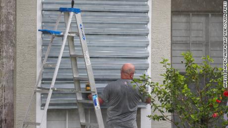 Martedì, un residente di Tampa chiude le finestre con le persiane in vista dell'uragano Elsa.