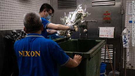 Flowers from the makeshift vigil for the attacker are thrown in the garbage on July 2.
