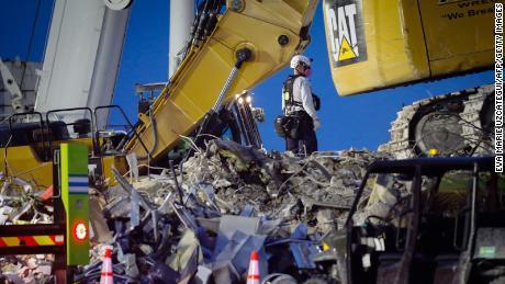 Спасательные команды противостоят ветру, молнии и жаре в 12-часовые смены, чтобы искать жертв обрушения здания во Флориде.