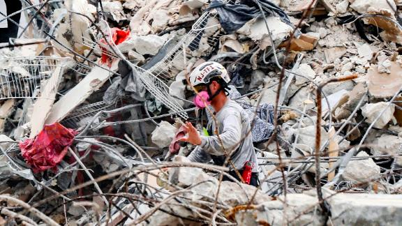 """A member of a search team moves rubble at the site on July 7. Authorities transitioned from search and rescue to search and recovery after determining """"the viability of life in the rubble"""" was low, Miami-Dade County Fire Chief Alan Cominsky said."""