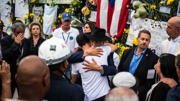 A member of Miami-Dade Fire Rescue hugs victims' family members and friends at the memorial near the collapsed building.