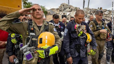 Members of the search and rescue teams gather for a moment of silence and prayer at the victims' memorial in the collapsed condo building of the South Champlain Towers on July 7.