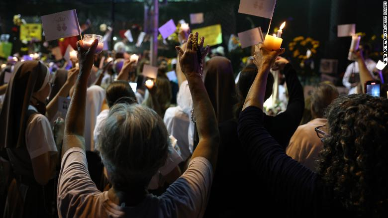 People lift their hands during a prayer at the memorial site for victims of the collapsed condo building.