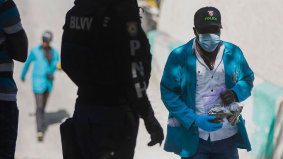 A forensic investigator carries a bagful of bullet casings collected at the residence of Haiti's President Jovenel Moise in Port-au-Prince, Haiti, on July 7.