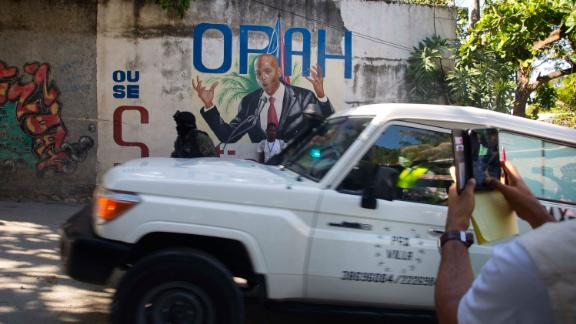 An ambulance carrying the body of Haiti's President Jovenel Moise drives past a mural featuring him near the leader's residence in Port-au-Prince, Haiti, on July 7.