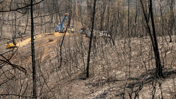 A utility crew works on power lines in front of a hillside that was burned by the Salt Fire in California's Shasta County.