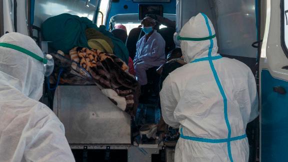 Des agents de santé arrivent avec un patient à l'établissement COVID-19 de l'hôpital universitaire Chris Hani Baragwanath, à Johannesburg, le lundi 21 juin 2021.