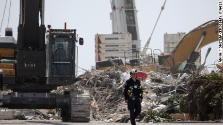 Рабочий покидает останки разрушенного многоквартирного дома 8 июля.