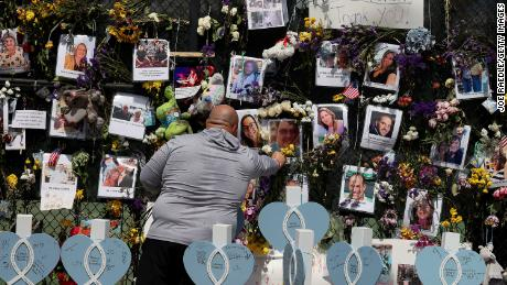 A man lays flowers at the memorial which includes photos of some of the victims of the Champlain Towers South condo building collapse on July 8.