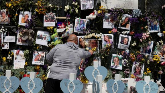 A man places flowers in the memorial that includes pictures of some of the victims of the collapsed Champlain Towers South condo building on July 8.