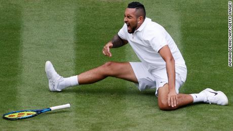 Australia's Nick Kyrgios falls as he returns to France's Ugo Humbert during their men's singles round on the third day of the 2021 Wimbledon Championship.