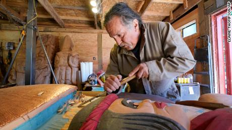 Lummi Nation lead carver Jewell James works on the final details of a nearly 25-foot totem pole to be gifted to the Biden administration at the end of July.