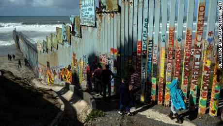 La gente camina cerca de la valla fronteriza en el Parque de la Amistad en Tijuana, México.