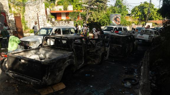 Burnt out cars line the street near the late President's residence in Haiti.