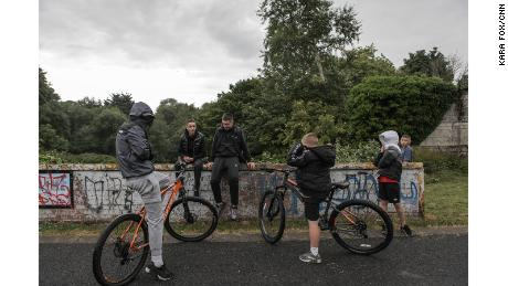 """Youths gather near a """"peace wall"""" in north Belfast's Alexandra Park. The peace wall, also referred to as a """"separation barrier,"""" is one of dozens of structures erected to separate predominantly republican and nationalist neighborhoods."""
