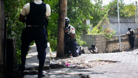 Police search the Morne Calvaire district of Petion-Ville for suspects who remain at large in the murder.