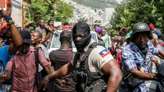 La gente vitorea cuando un coche de policía pasa por la comisaría de policía donde hombres armados presuntamente implicados en el asesinato del presidente Jovenel Moise fueron detenidos en Puerto Príncipe el 8 de julio.