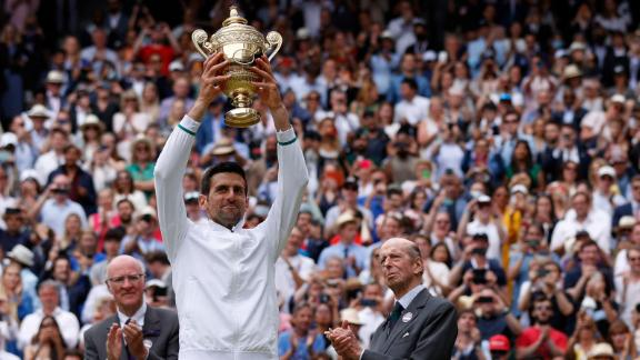 Serbia's Novak Djokovic, with Britain's Catherine (R), Duchess of Cambridge, holds the winner's trophy after beating Italy's Matteo Berrettini.