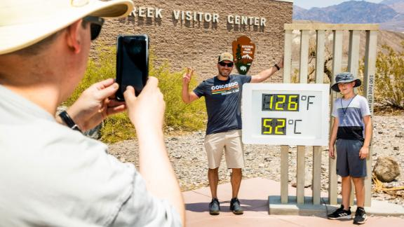 """Visitors take photos in front of a thermometer July 10 at Death Valley National Park in Death Valley, California. Death Valley is known to be a hot place, but on July 9 <a href=""""https://www.cnn.com/2021/07/11/weather/weather-death-valley-heat-record-california-weekend/index.html"""" target=""""_blank"""">it hit 130 degrees Fahrenheit</a> for only the fifth time in recorded history."""