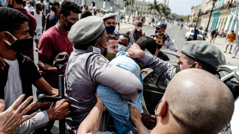 """Un bărbat este arestat în timpul unei manifestații împotriva guvernului președintelui cubanez Miguel Diaz-Canel la Havana, la 11 iulie 2021. - Mii de cubanezi au participat duminică la rare proteste împotriva guvernului comunist, mărșăluind printr-un oraș scandând """"Jos cu dictatură """"și"""" Vrem libertate """". (Fotografie de ADALBERTO ROQUE / AFP) (Fotografie de ADALBERTO ROQUE / AFP prin Getty Images)"""
