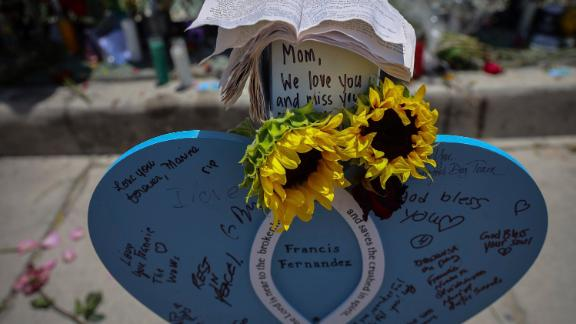 Wooden hearts with victims' names have been put up at the memorial site near the building's remains.