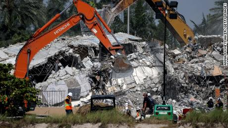 Excavators dig through the remains from the collapsed Champlain Towers South condo building.