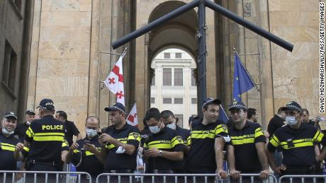 Police officers observe a rally outside the offices of the Georgian Parliament following the death of TV Pirveli journalist Alexander Lashkarava.