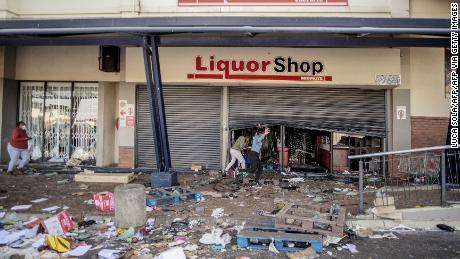 Rioters run from police officers after looting a liquor shop at the Jabulani Mall in the Soweto district of Johannesburg on Monday.
