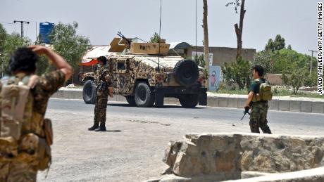 Des agents de sécurité afghans montent la garde le long d'une route lors d'un combat entre les forces afghanes et les combattants talibans à Kandahar le 9 juillet.