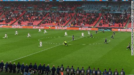 Players kneel before the UEFA Euro 2020 Group D football match between England and Scotland at Wembley Stadium in London.