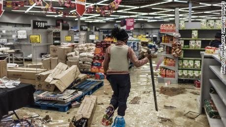 A police officer inspects the damage at a looted mall in Vosloorus, South Africa, on Tuesday.