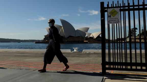 A pedestrian wearing a face mask walks past the Sydney Opera House in Sydney on July 13, 2021. The city is currently in lockdown to curb a fast-growing coronavirus outbreak.